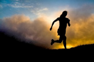 A woman runs on a trail silhouetted by a setting sun shrouded by fog.